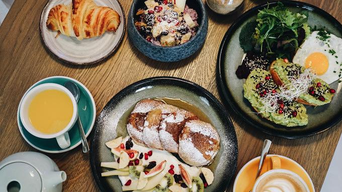 Frühstück aus Avocado-Brot, Pancakes, Kaffee, Croissants im Café im Herz und Zucker.